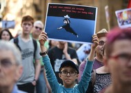 A young demonstrator holds up a sign to support migrant refugees lo ...