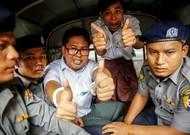 Les journalistes de Reuters, Wa Lone (C) et Kyaw Soe Oo, font un geste alors qu'il ...