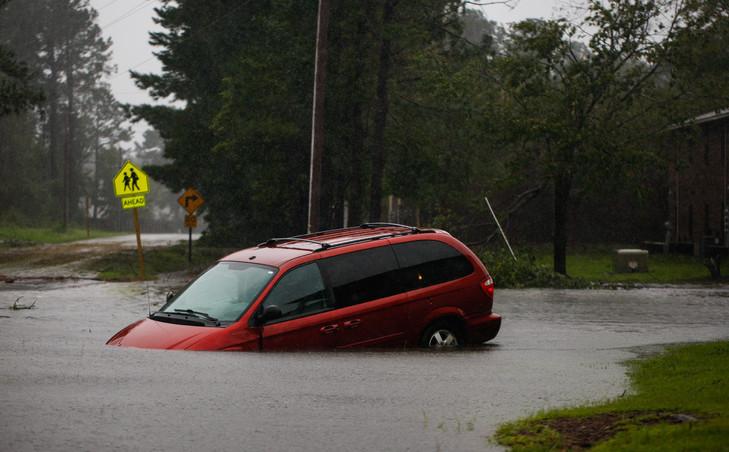 Une voiture abandonnée sur une route inondée près de New Bern, en Caroline du Nord, le 14 septembre 2018 après le passage de l'ouragan Florence sur la côte sud-est / AFP