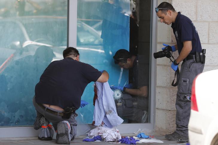 Palästinensische Ermittler untersuchen, wo ein Israeli am 16. September 2018 / AFP von einem Palästinenser in der Nähe des Eingangs eines Einkaufszentrums im besetzten Westjordanland tödlich getroffen wurde