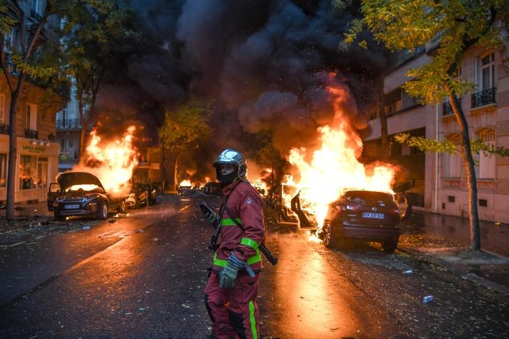 Un pompier devant des voitures en feu, lors des manifestations des«gilets jaunes», samedi 1er décembre à Paris.