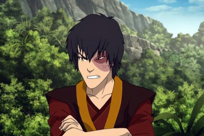 Prince Zuko from Avatar: The Last Airbender, scowling with arms folded against a background of forested cliffs.