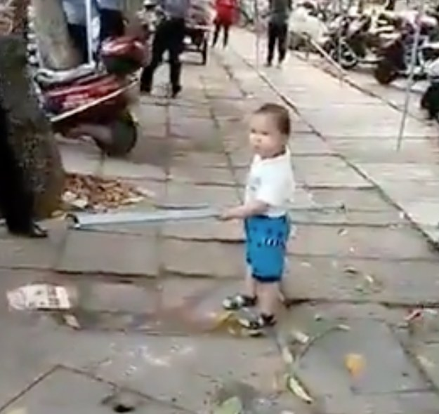 In the video, the unnamed boy approaches a group of Chengguan in a marketplace. The Chengguan are urban management and code enforcers in China. The grandmother's setup was allegedly taking up too much sidewalk space.