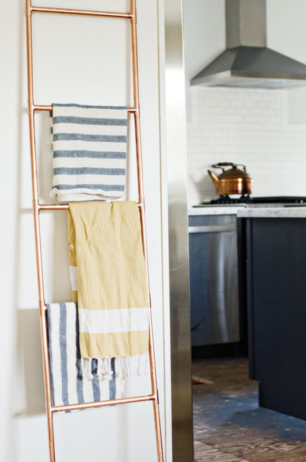 Assemble a ladder using copper piping and use it to hang tea towels and dishcloths on.