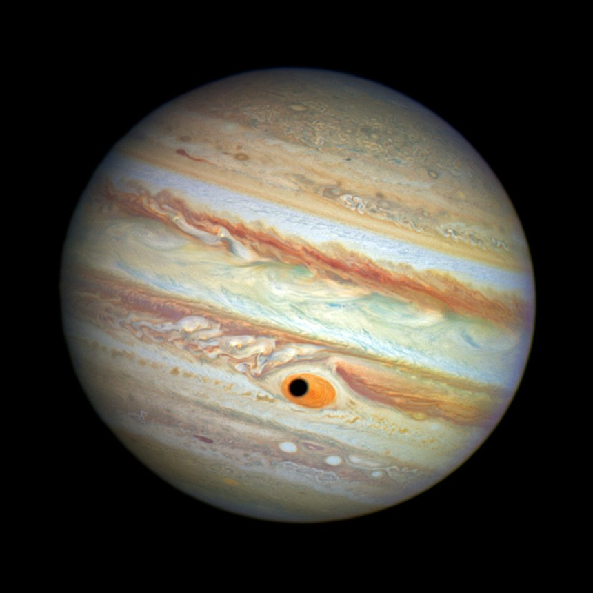 "Hubble was monitoring changes in Jupiter's immense GRS storm on April 21, 2014, when the shadow of the Jovian moon, Ganymede, swept across the center of the storm. This gave the giant planet the uncanny appearance of having a pupil in the center of a 10,000-mile-diameter ""eye."" For a moment, Jupiter ""stared"" back at Hubble like a giant Cyclops."