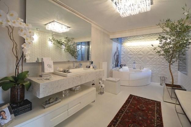 Um banheiro de rico desses, tão grande que cabe tapete, plantas, flores, retratos de família...