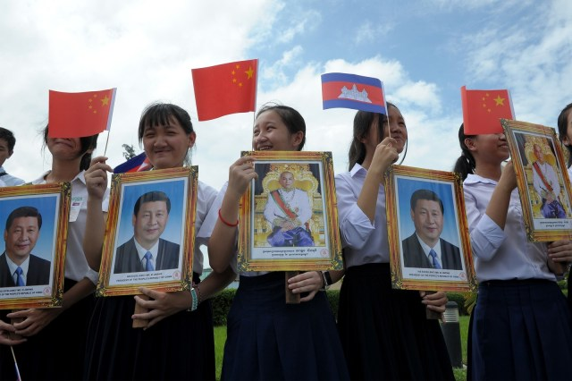 Students hold photos of Xi Jinping and King Norodom Sihamoni during Xi's visit to Cambodia in October.