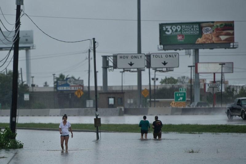 Personas caminando por calles inundadas luego del paso del huracán Harvey, 27 de agosto de 2017 en Houston.