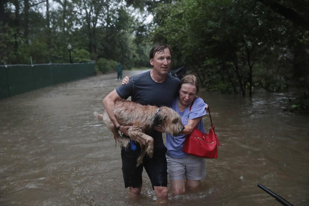 Andrew White (izquierda) ayuda a una vecina en la calle luego de rescatarla de su hogar con su bote en el lujoso vecindario de River Oaks, luego de que fuera inundado por el paso del huracán Harvey el 27 de agosto de 2017, en Houston.