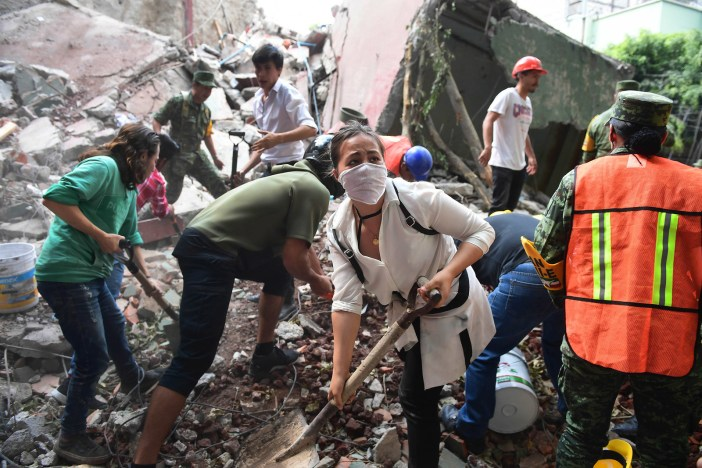 Rescuer and volunteers dig through the rubble and debris from a collapsed building.