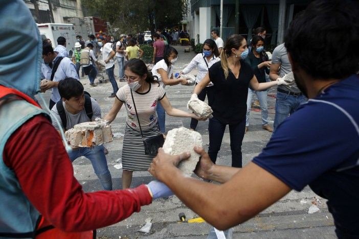 Volunteers pick up the rubble from a building that collapsed during an earthquake in the Condesa neighborhood of Mexico City.