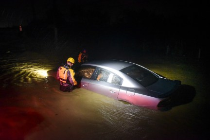 Rescue staff from the Municipal Emergency Management Agency investigate an empty flooded car during the passage of Hurricane Irma through the northeastern part of the island in Fajardo.