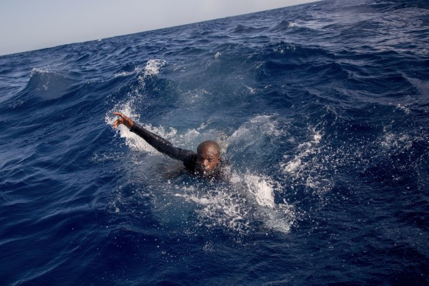 Rescuers and photographers watched as refugees began falling overboard as the patrol boat tried to leave with people still clinging to its sides.
