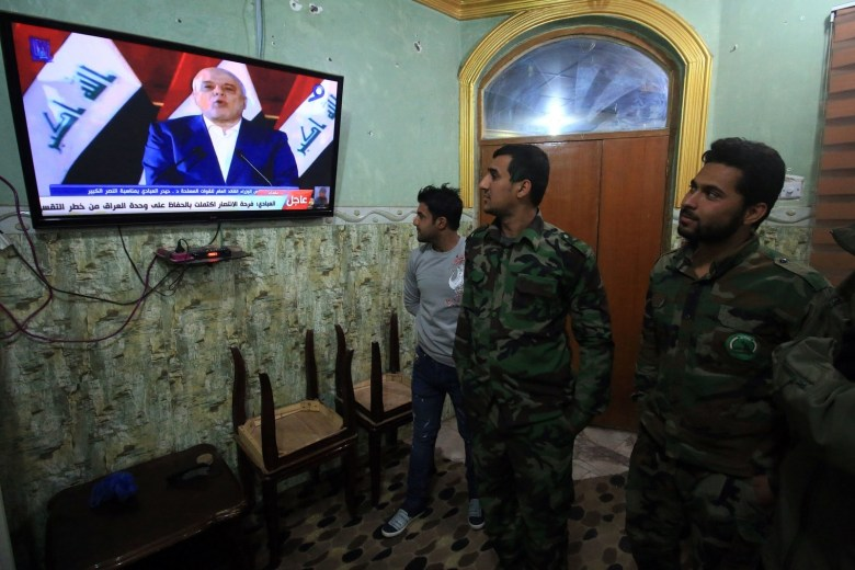 Members of the Hashed al-Shaabi watch the televised statement of Prime Minister Haider al-Abadi in Basra on Saturday.