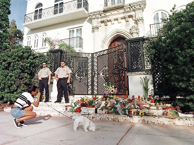 A woman paused with her dog to take a picture of the memorial forming outside Versace's home.