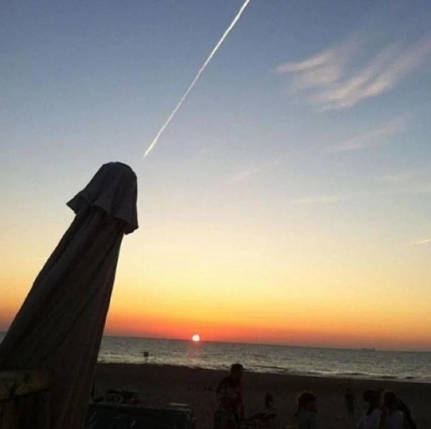 Technically, this is just a beach umbrella and the contrail of a passing jet, not an ejaculating penis.