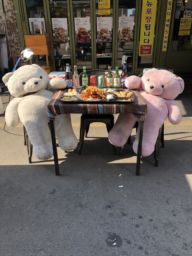 A restaurant featuring two giant stuffed bears eating food.
