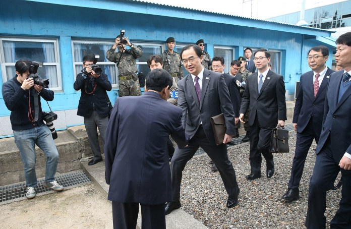 South Korean Unification Minister Cho Myoung-gyun (centre) crosses the Korean border line to attend a high-level talks at the border village of Panmunjom on Thursday.