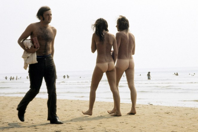 A pair of naked hippies stroll on the beach during the Isle of Wight Festival in 1969.