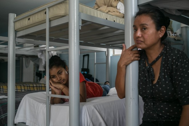 Patricia (left) and Maria sit in their beds at the shelter and watch as children play with one another.