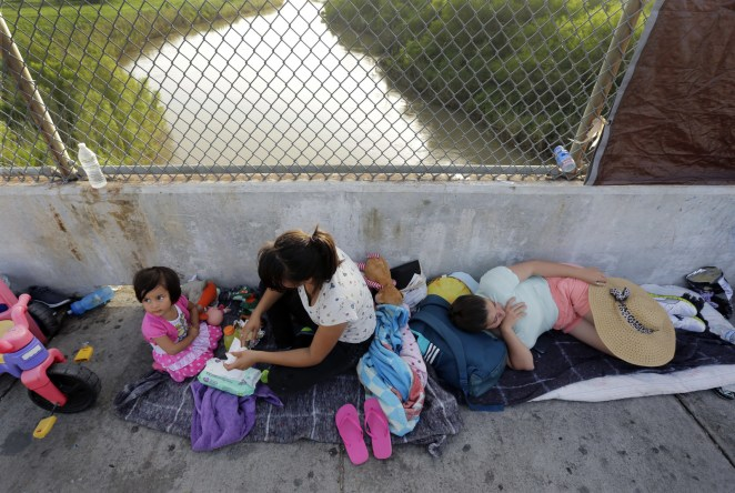 Immigrants from Cuba and Guatemala seeking asylum in the United States wait on the Matamoros International Bridge above the Rio Grande on June 29, 2018.