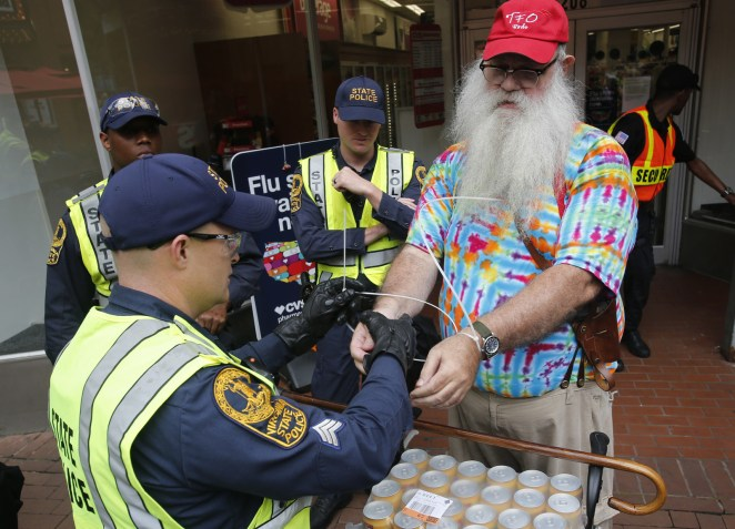 State Police arrest a local resident, John Miska, in the locked down downtown area in Charlottesville, Va., Saturday, Aug. 11, 2018. Miska purchased razor blades, which are banned items, in a downtown drugstore.