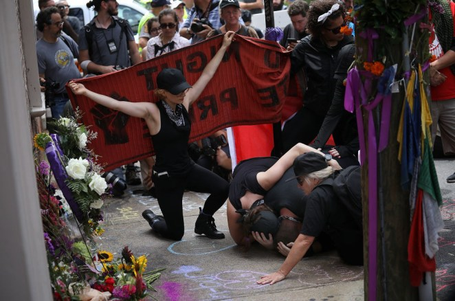 Anti-fascist protesters mourn at the site of a makeshift memorial where Heather Heyer was killed last year on August 11, 2018 in Charlottesville, Virginia.