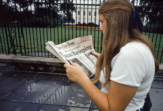 A woman reads a headline in front of the White House on the afternoon of Nixon's resignation speech.