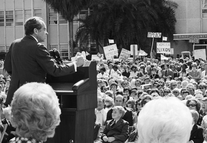 President Nixon addresses a dedication ceremony of a new health care center in Miami. In the background, protesters carry signs calling for his impeachment.