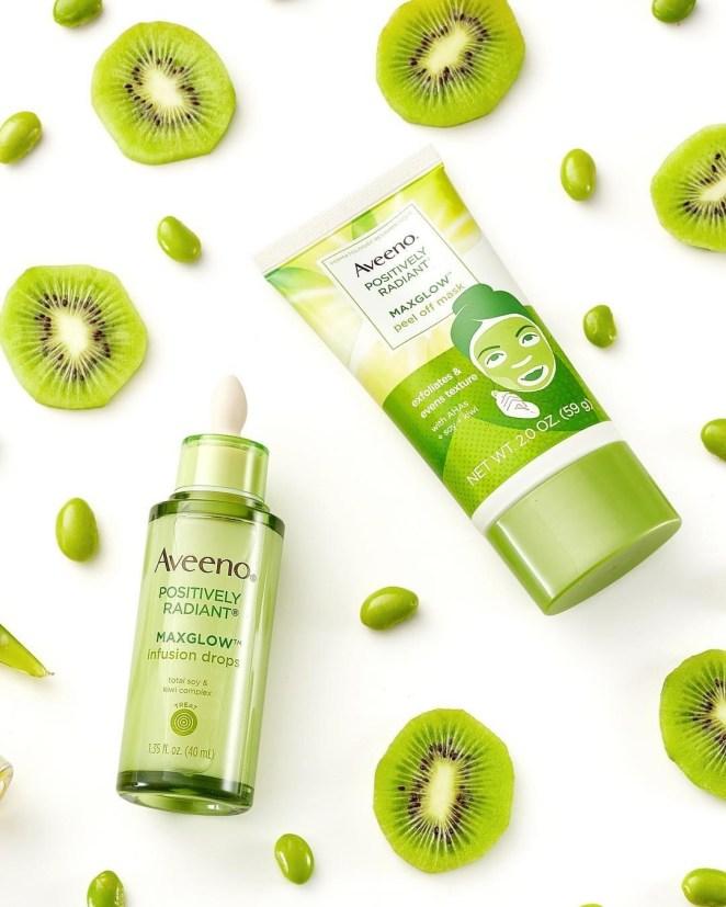 Bottle of Aveeno mask styled on a table with kiwi
