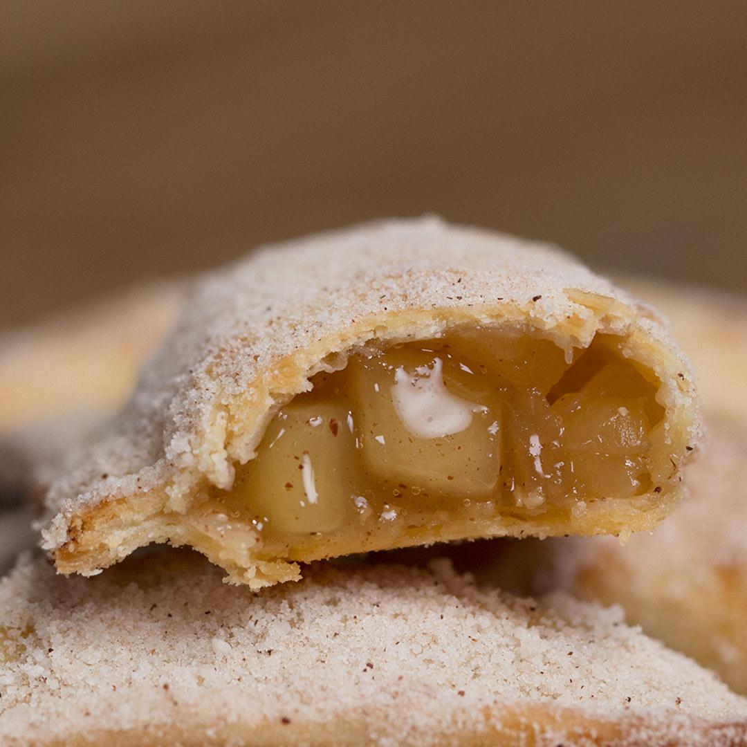 Você vai precisar de:3 maçãs descascadas e picadas½ xícara de chá de açúcar refinado¼ de colher de chá de canela em pó½ colher de chá de essência de baunilha1 colher de sopa de amido de milho1 rolo de massa de pastel frescaManteiga sem sal derretida para untar1 ovo batidoAçúcar refinado para cobrirCanela em pó para cobrirModo de preparo:1. Numa panela média, misture as maçãs picadas e o açúcar. Cozinhe por 10 minutos em fogo médio ou até as maçãs ficarem macias.2. Adicione a canela em pó e a essência de baunilha.3. Misture o amido de milho e cozinhe por 5-7 minutos ou até engrossar a calda.4. Deixe esfriar o recheio.5. Corte a massa de pastel em retângulos de 12x10cm e colocar 1 colher de sopa do recheio. 6. Passe água nas bordas da massa e feche no sentido da largura, pressionando com a ponta de um garfo.7. Preaqueça o forno à 200°C.8. Unte uma assadeira com manteiga derretida e disponha as tortinhas sobre.9. Pincele cada tortinha com manteiga derretida e ovo batido.10. Leve ao forno por 15-20 minutos ou até ficarem douradas. Retire do forno e pincele manteiga derretida.11. Numa tigela, misture açúcar refinado e canela, passando cada tortinha na mistura até cobrir.12. Sirva quente ou em temperatura ambiente, aproveite!