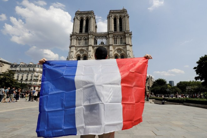 A France supporter holds a French flag in front of Notre Dame Cathedral, prior to the start of the Russia 2018 World Cup final football match between France and Croatia, in Paris on July 15, 2018.