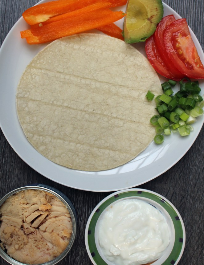 1 can albacore tuna fish, drained1 tablespoon plain Greek yogurt⅙ bell pepper, diced1 chopped scallion, white and light green parts onlyKosher salt, to tasteFreshly ground black pepper, to taste1-2 corn tortillas¼ avocado, sliced⅙ tomato, thinly sliced