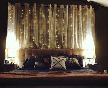 a reviewer's photo of the twinkle lights hanging behind their bed