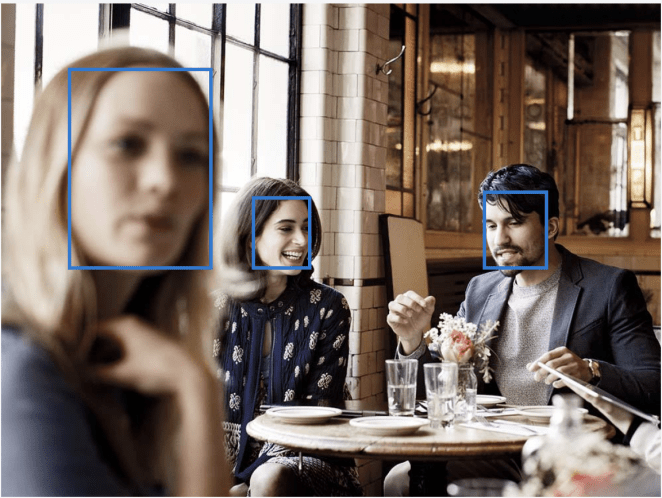 This photo shows people at a restaurant with squares around their faces, ostensibly highlighting the ability of Microsoft's Azure facial recognition service.