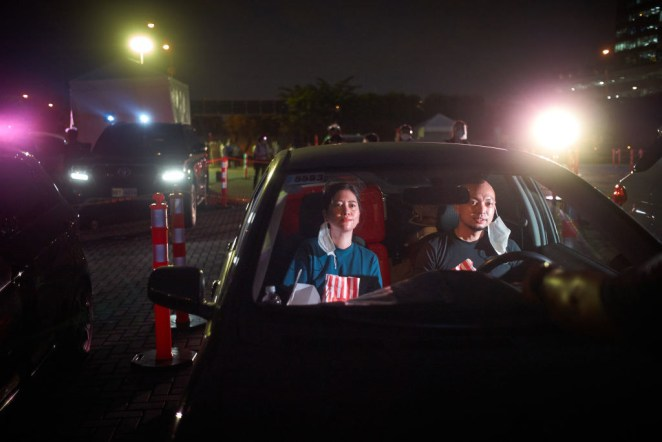 A couple at a drive-in movie wearing face masks