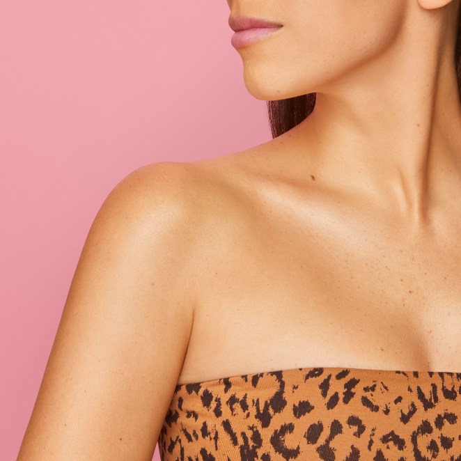 Model wearing oil on shoulder and collarbone to show the subtle shimmer it leaves behind