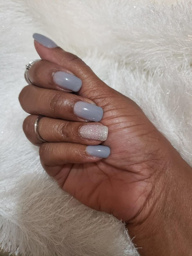 Reviewer with periwinkle nails and glittery white accent nail