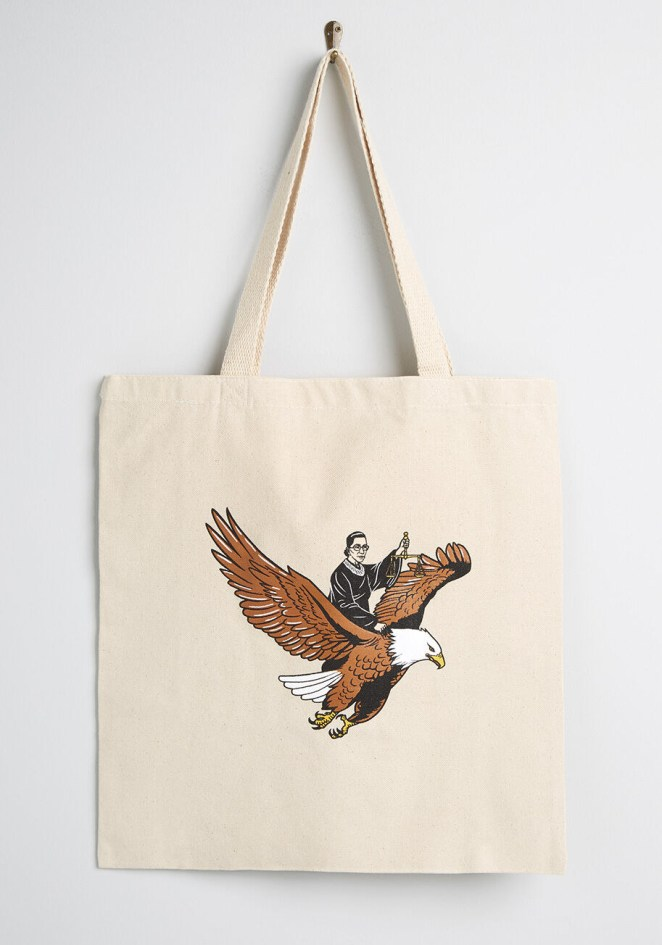 A canvas tote bag hanging on a hook featuring a print of Ruth Bader Ginsburg riding an eagle and holding a scale