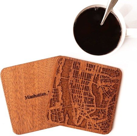 Brown Manhattan coasters sit beside a white cup of coffee