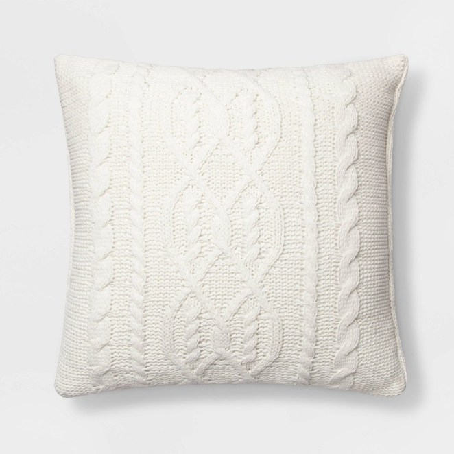 A white throw pillow with a cable knit pattern on it