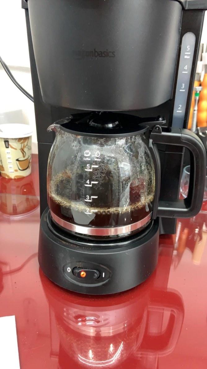 İnceleyen kişinin bir demlik kahve yapan kahve makinesinin fotoğrafı