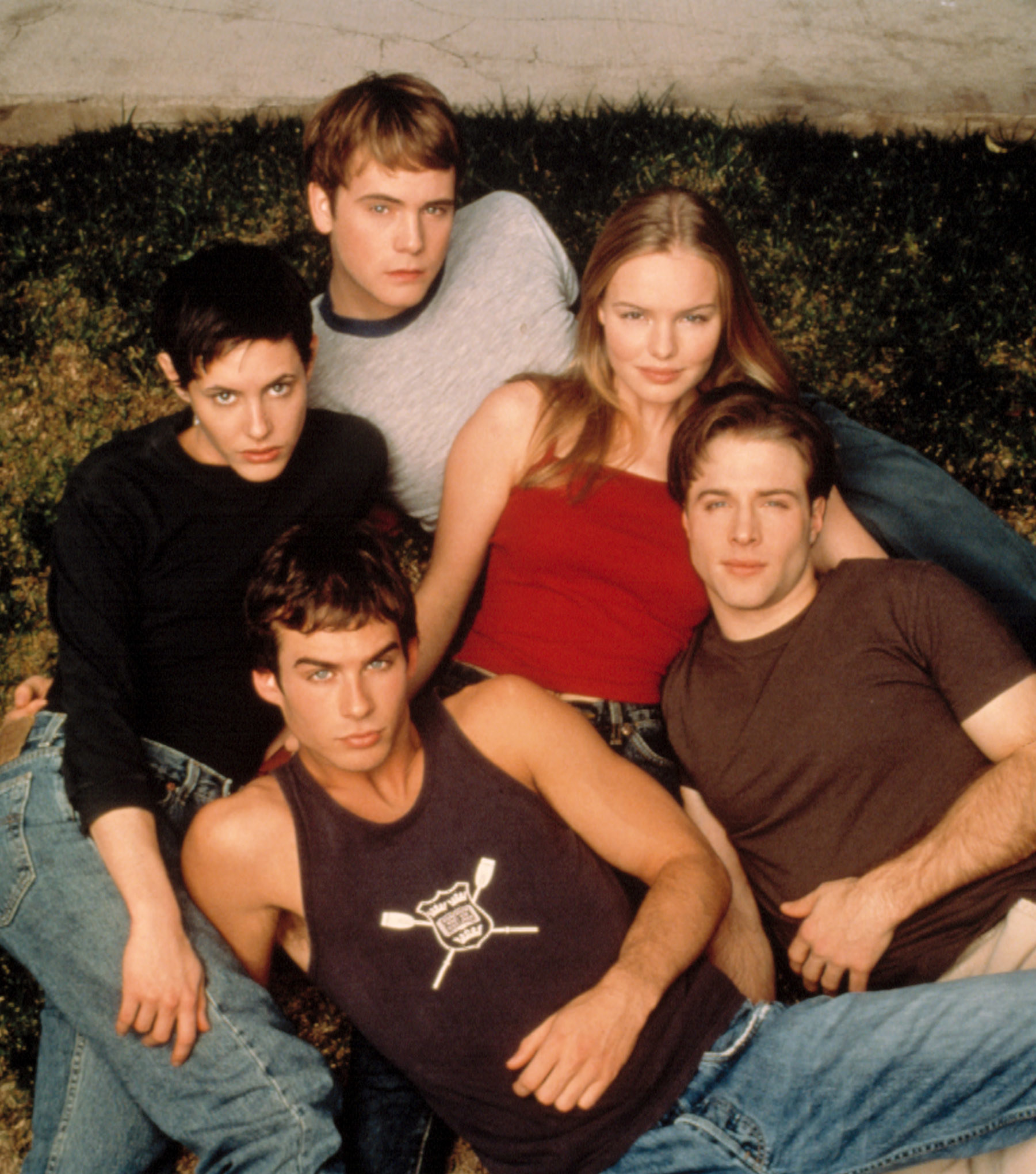 The five cast members posing on the ground