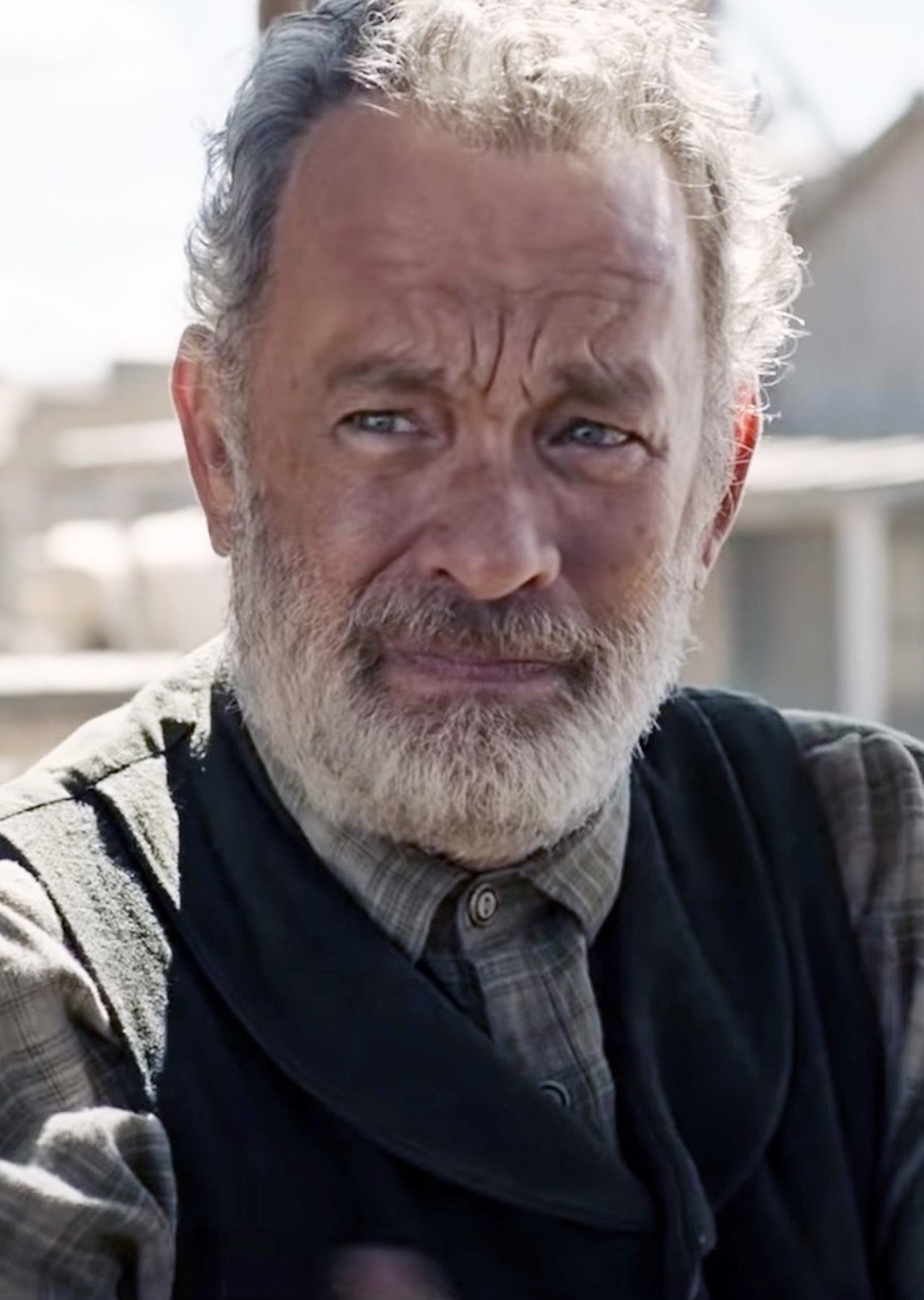 Tom Hanks with a grey beard, wearing a flannel shirt and sweater vest