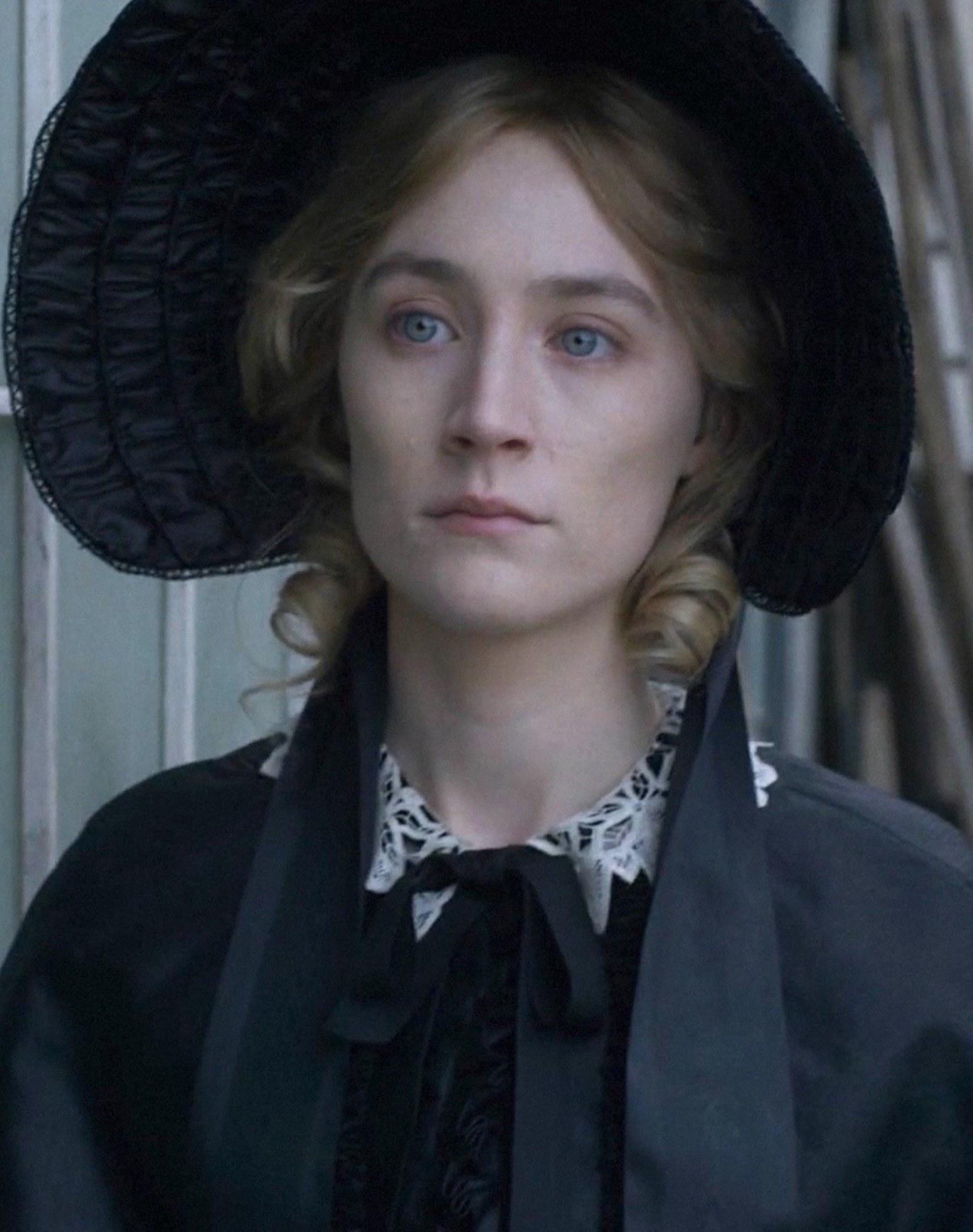 Saoirse Ronan wearing a wide brimmed hat, looking gloomy