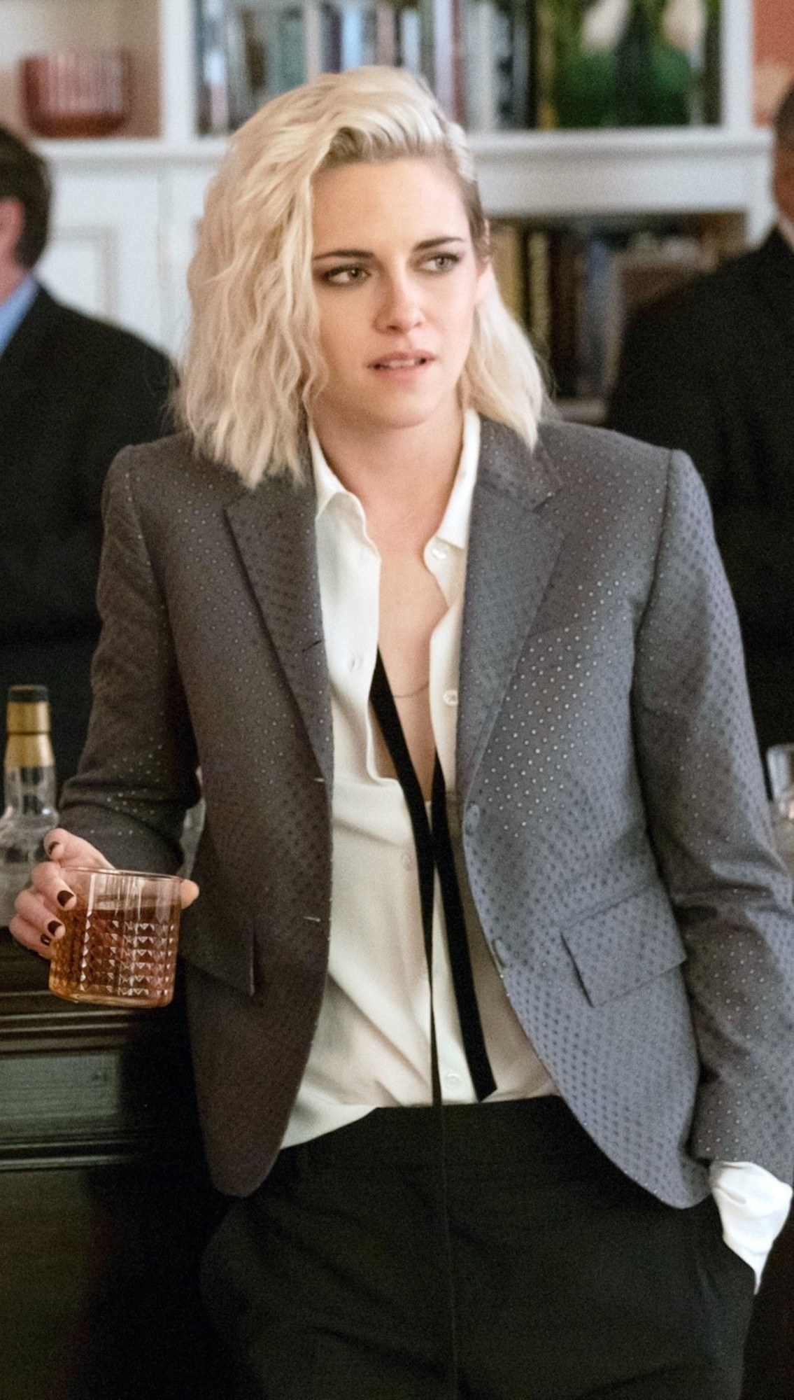 Kristen Stewart leaning up against a bar while holding a cocktail