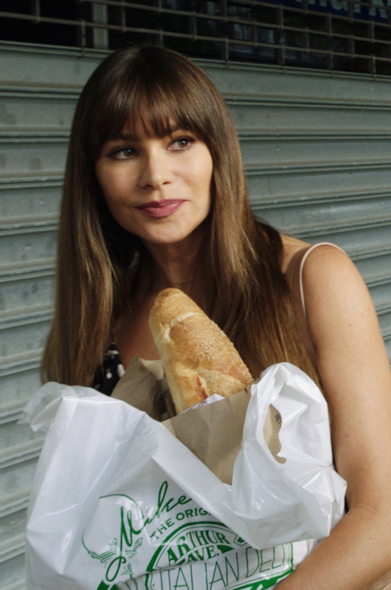 Sofia Vergara with long hair and bangs, carrying groceries on the street