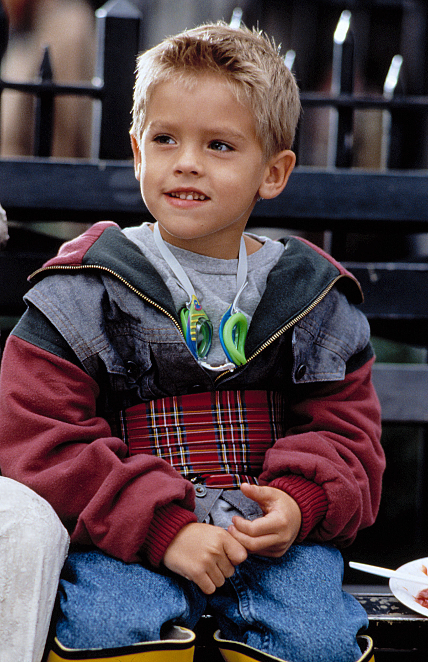 A young Cole Sprouse sitting on a park bench in New York City