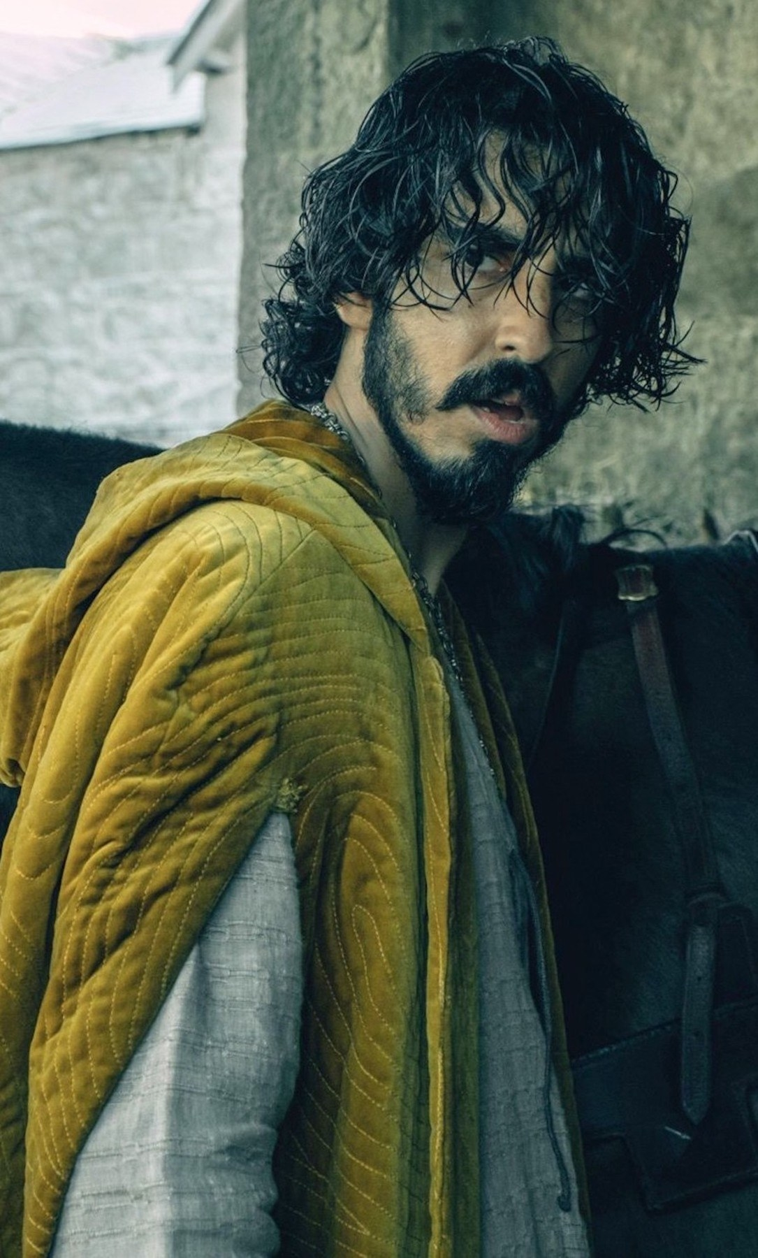 Dev Patel with long hair, a beard, standing next to a horse looking scruffy