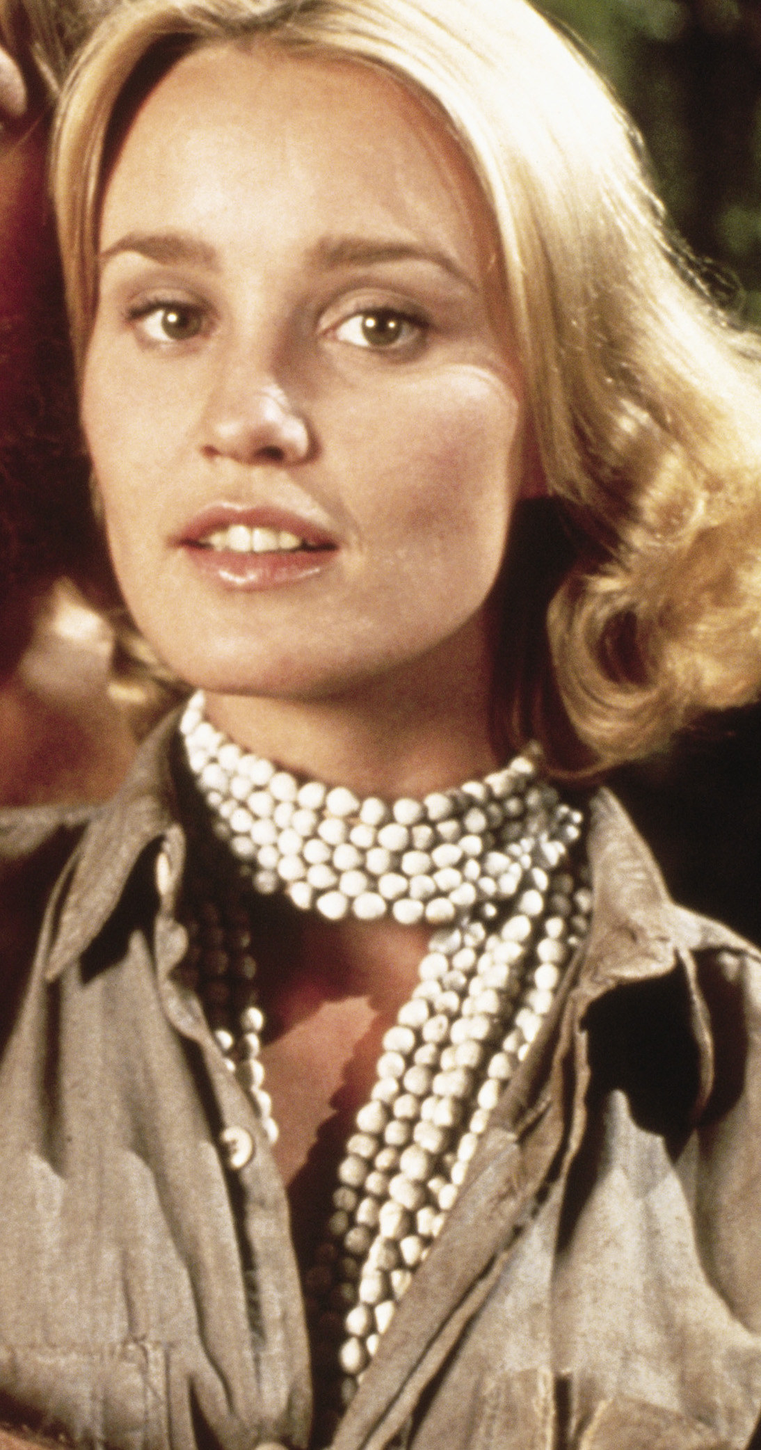 Jessica Lange with short curly hair while wearing long pearls